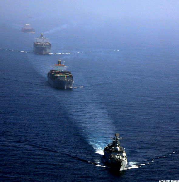 Warships escort merchant vessels in Gulf of Aden.