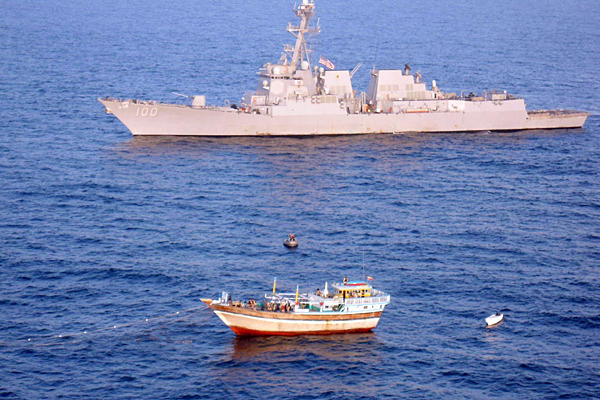 In 2011, the foreign navies amassed around the Horn of Africa and NW Indian Ocean moved away from playing a losing game of catch-up against Somali pirates and went instead to a game of offensive defense. Meaning that surveillance was increased, and suspiciously acting dhows towing skiffs, as well as other odd behavior by fishing boats was tracked and in the most glaring cases a warship was sent to go inspect. In this case we see a dhow towing a skiff that's been stopped by a USN warship - a team is moving towards the dhow, while the cameraman sits in a helicopter that likely carries a marksman with a large caliber sniper rifle who is providing cover for the inspection team. This new strategy by the navies has been one of the main reasons - along with greater numbers of merchant vessels respecting BMP4 and more armed guards on board ships - Somali pirates have had to change their game and get a lot craftier.